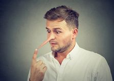 Hombre joven chocado preocupante con la nariz larga Concepto del mentiroso fotos de archivo
