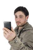 Hombre joven chocado que comprueba su smarphone aislado Imagenes de archivo