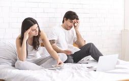 Hombre joven chocado que mira los controles, presupuesto familiar de planificación fotografía de archivo