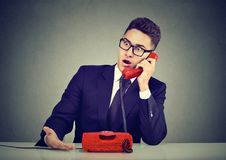 Hombre joven chocado que recibe malas noticias sobre el teléfono foto de archivo libre de regalías