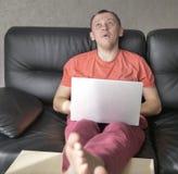Hombre joven chocado que se sienta en el sofá con un ordenador portátil foto de archivo libre de regalías