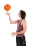 Hombre joven con baloncesto de giro en su índice Imágenes de archivo libres de regalías