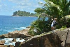 Hombre joven con caminar el polo y la mochila que se colocan en nea grande de la roca Fotos de archivo libres de regalías