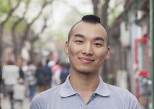 Hombre joven con corte de pelo del Mohawk que sonríe mirando la cámara Imagen de archivo