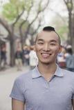 Hombre joven con corte de pelo del Mohawk que sonríe mirando la cámara Foto de archivo
