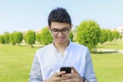 Hombre joven con desgaste del ojo en el jardín que manda un SMS en teléfono elegante Foto de archivo