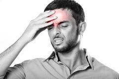 Hombre joven con dolor de cabeza y jaqueca sufridores de la barba en la expresión del dolor foto de archivo