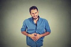 Hombre joven con dolor de estómago fotos de archivo