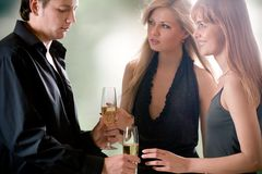 Hombre joven con dos vidrios con la colocación del champán y de dos mujeres Imagen de archivo libre de regalías