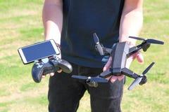 Hombre joven con el abejón teledirigido del control del teléfono celular Verde soleado Imagen de archivo