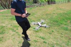 Hombre joven con el abejón teledirigido del vuelo del teléfono celular Gre soleado Foto de archivo libre de regalías