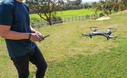 Hombre joven con el abejón teledirigido del vuelo del teléfono celular Gre soleado Imágenes de archivo libres de regalías