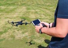 Hombre joven con el abejón teledirigido del vuelo del teléfono celular Gre soleado Foto de archivo