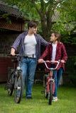 Hombre joven con el adolescente que se coloca con las bicicletas en el patio trasero de la casa Foto de archivo libre de regalías