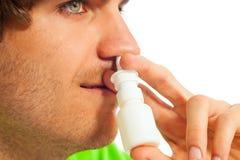 Hombre joven con el aerosol nasal Fotos de archivo