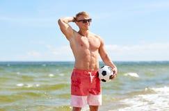 Hombre joven con el balón de fútbol en la playa Imágenes de archivo libres de regalías