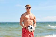 Hombre joven con el balón de fútbol en la playa Imagen de archivo libre de regalías