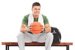 Hombre joven con el baloncesto que se sienta en un banco Fotos de archivo libres de regalías