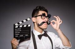 Hombre joven con el bigote falso que sostiene clapperboard fotografía de archivo libre de regalías