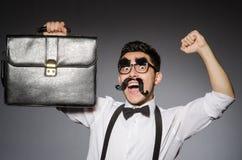 Hombre joven con el bigote falso que sostiene el caso imagen de archivo libre de regalías