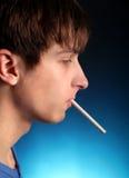 Hombre joven con el cigarrillo Foto de archivo libre de regalías