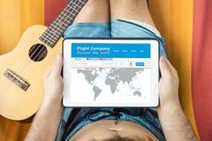 Hombre joven con el dispositivo de la tableta que consulta un sitio web que viaja, mintiendo en una hamaca Imagen de archivo