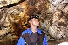 Hombre joven con el faro en una cueva Imagenes de archivo