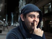 Hombre joven con el finger en su nariz Foto de archivo libre de regalías