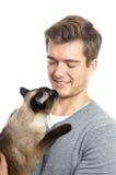 Hombre joven con el gato siamés Foto de archivo