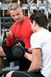 Hombre joven con el instructor en la gimnasia Foto de archivo libre de regalías