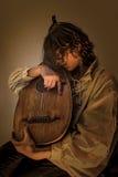 Hombre joven con el laúd viejo de la guitarra de Oud Foto de archivo