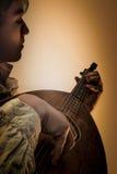 Hombre joven con el laúd viejo de la guitarra de Oud Fotos de archivo libres de regalías