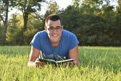 Hombre joven con el libro de lectura de los vidrios en el parque Fotos de archivo libres de regalías