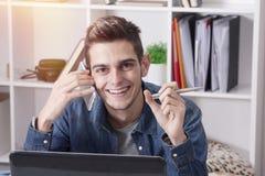 Hombre joven con el móvil y el ordenador Fotografía de archivo libre de regalías