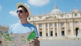 Hombre joven con el mapa de la ciudad en la Ciudad del Vaticano y la iglesia de la basílica de San Pedro, Roma, Italia Hombre tur almacen de metraje de vídeo