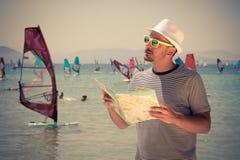 Hombre joven con el mapa en la playa Foto de archivo libre de regalías