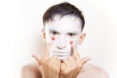 Hombre joven con el maquillaje blanco y corazones rojos en cara Fotografía de archivo libre de regalías
