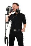 Hombre joven con el micrófono en el fondo blanco Fotografía de archivo libre de regalías