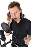 Hombre joven con el micrófono en el fondo blanco Imagenes de archivo