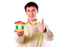 Hombre joven con el modelo de la casa. imagen de archivo
