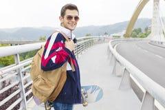 Hombre joven con el monopatín en la calle Fotografía de archivo libre de regalías