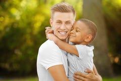 Hombre joven con el muchacho afroamericano adoptado Fotos de archivo libres de regalías
