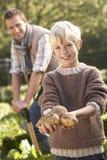Hombre joven con el niño que trabaja en jardín Imágenes de archivo libres de regalías