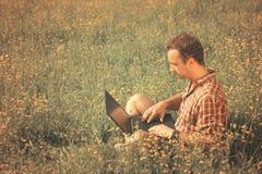 Hombre joven con el ordenador portátil al aire libre Fotografía de archivo