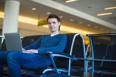 Hombre joven con el ordenador portátil en el aeropuerto mientras que espera Imagen de archivo libre de regalías