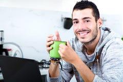 Hombre joven con el ordenador portátil en la cocina foto de archivo