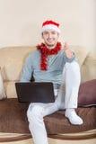 Hombre joven con el ordenador portátil en un sofá Hombre de negocios con el sombrero de santa Foto de archivo libre de regalías
