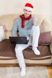 Hombre joven con el ordenador portátil en un sofá Hombre de negocios con el sombrero de santa Fotos de archivo