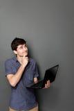 Hombre joven con el ordenador portátil que mira para arriba para copiar el espacio Imagen de archivo libre de regalías