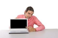 Hombre joven con el ordenador portátil que señala en el monitor sobre el backgro blanco Imagenes de archivo